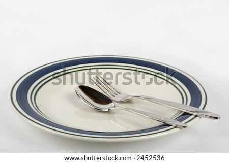 Spoon and fork on a plate - stock photo