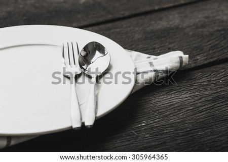 spoon and fork on plate and on a table - stock photo