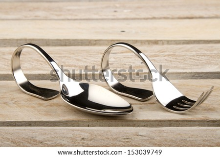 Spoon and fork with bent handles on wood surface - stock photo