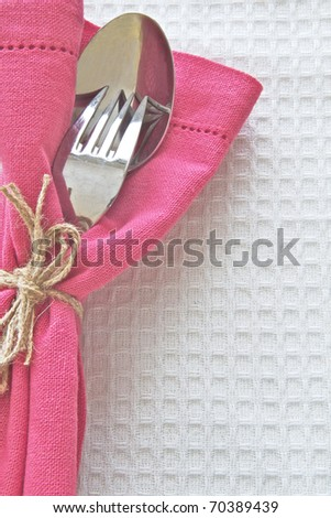 Spoon and fork with pink serviette on white linen cloth - stock photo