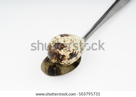 Spoon and quail egg with white background