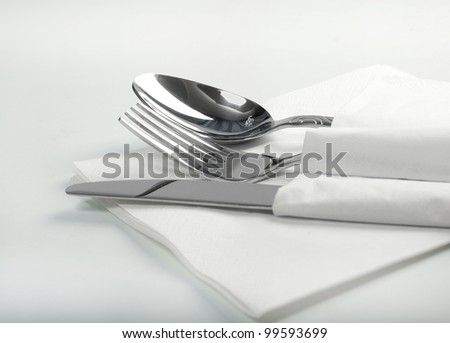 Spoon, fork and a knife lie on serviette.on a white background - stock photo