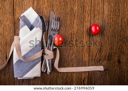 Spoon, fork and a knife with napkin on wood table decor with red tomatoes - stock photo