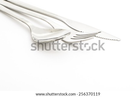 spoon, fork and knife at the top left on white background - stock photo
