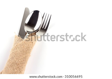 spoon, fork and knife stacked up on a sackcloth. - stock photo