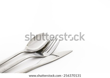 spoon, fork and knife to the lower left on white background