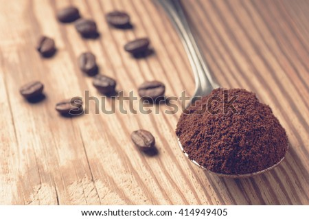 Spoon full of ground coffee and scattered coffee beans on rustic wooden board, shallow depth of field focused on ground coffee, vintage filtered - stock photo
