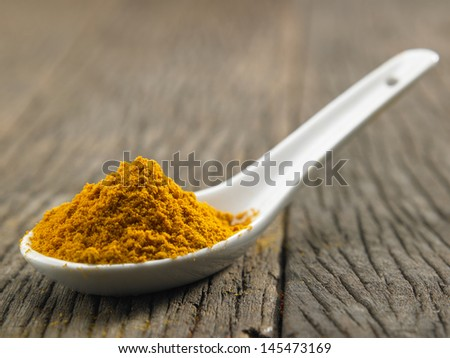 spoon full of the turmeric powder - stock photo