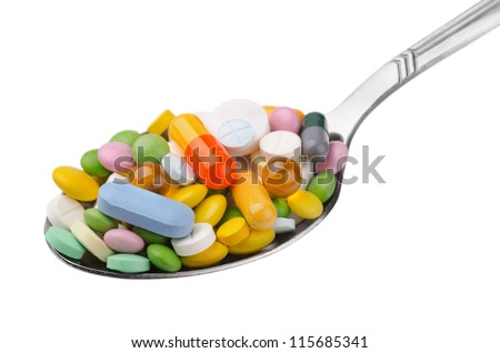 Spoon full of various colorful drugs isolated on white - stock photo
