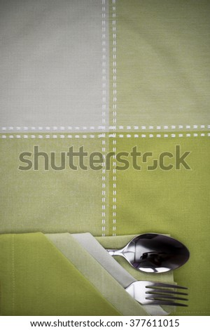 Spoon green tablecloth and Fork on the table - stock photo