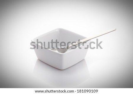 spoon in a square bowl isolated on a white background