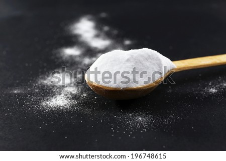 Spoon of baking soda on black background - stock photo