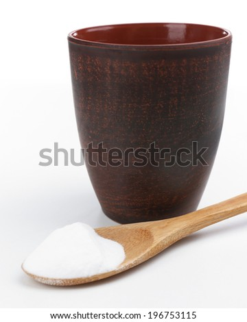Spoon of baking soda over glass of water, isolated on white - stock photo