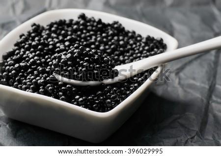 spoon of black caviar in a white bowl horizontal - stock photo