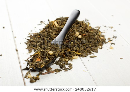 Spoon of dried green tea leaves on wooden background - stock photo