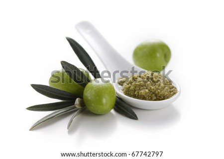 Spoon of green olive pate with olives and leaves on white background - stock photo