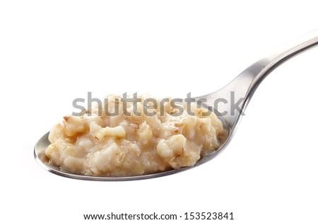 Spoon of oats porridge on a white background. Healthy breakfast - stock photo