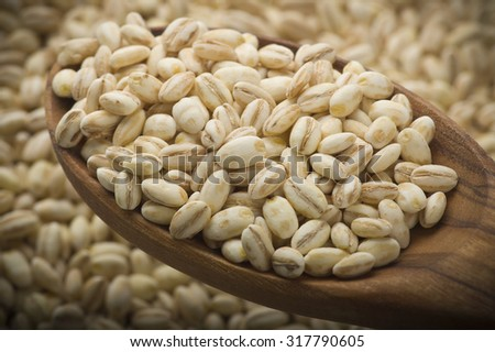 Spoon of Pearl barley close up on a table  - stock photo