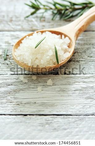 Spoon of sea salt closeup over wood background - stock photo