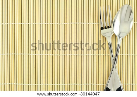 Spoon on bamboo background - stock photo