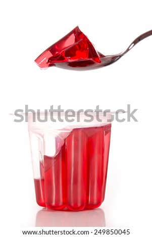 Spoon on red gelatin - stock photo