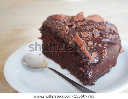 spoon on the side of a slice of chocolate sponge with chocolate icing