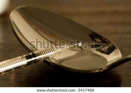 spoon used to prepare heroine, with hypodermic syringe - stock photo