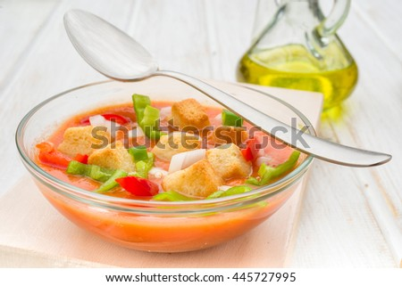 Spoon vegetables and gazpacho soup round glass bowl