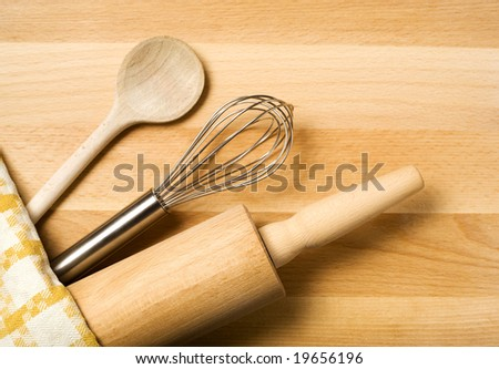 spoon, whisker, rolling pin, towel on wooden board - stock photo