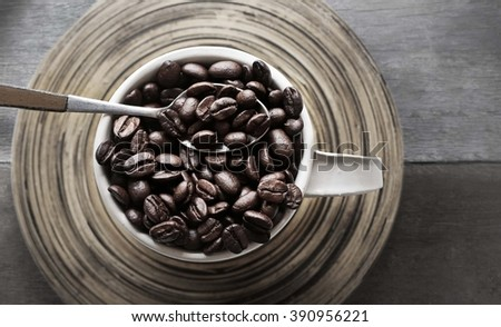 Spoon with a cup of coffee on a wooden table top view  - stock photo