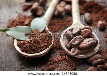 Spoon with aromatic cocoa powder and green leaf on scratched wooden background, close up - stock photo