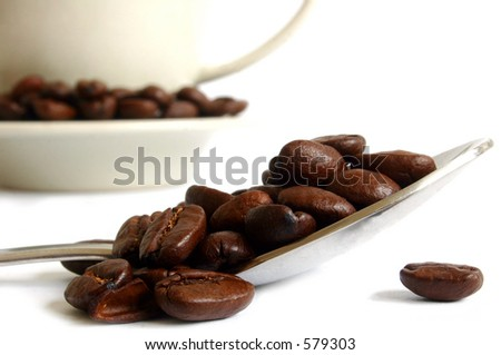 Spoon with coffee beans and mug ; isolated