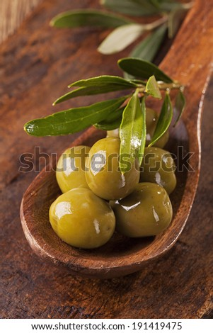 Spoon with green olives on a wooden table