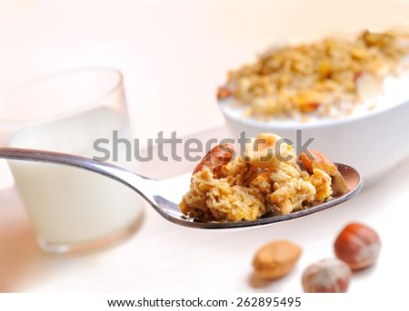 Spoon with muesli and nuts and glass of milk and cereal bowl at the bottom - stock photo