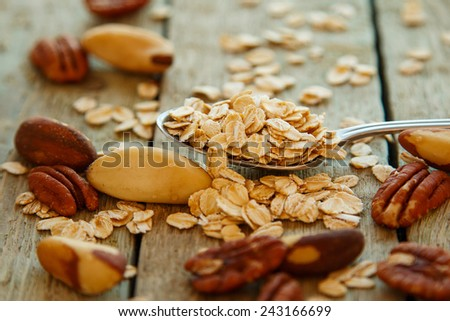 Spoon with oatmeals on wooden table - stock photo