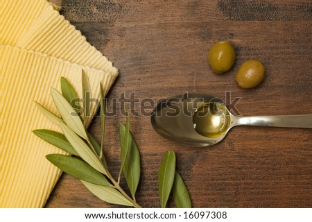 Spoon with Olive Oil on Wood Table - stock photo