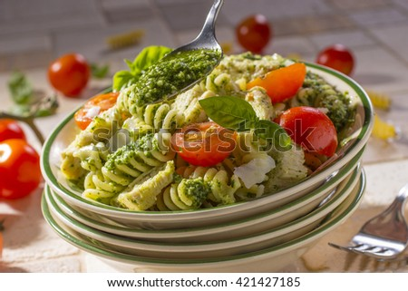 Spoon with Pesto Sauce over Bowl of Chicken Pesto Pasta