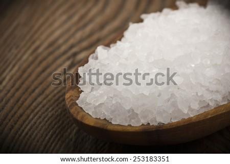 spoon with sea salt on wood table  - stock photo