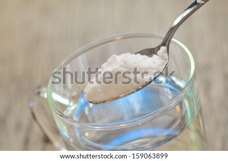 Spoonful of baking soda and glass of water - stock photo