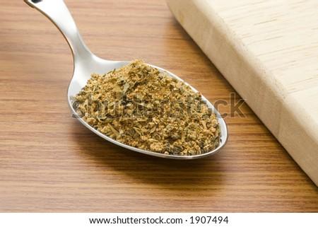 Spoonful of cajun seasoning besides a chopping board - stock photo