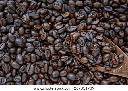 Spoonful of coffee beans on coffee bean heap - border design - stock photo