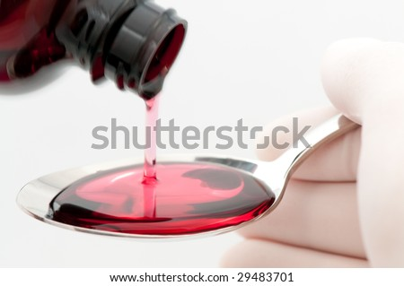 Spoonful of cough syrup being filled by person wearing latex gloves, on white background