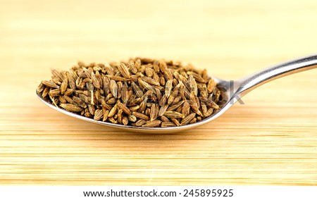 Spoonful of cumin seeds against wooden background - stock photo