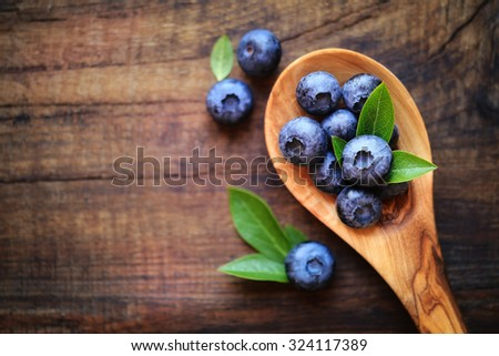 Spoonful of fresh ripe garden blueberries on dark rustic wooden table. with copy space for your text - stock photo