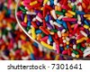 Spoonful of rainbow sprinkles with additional sprinkles in soft focus as the background.  Abstract macro with shallow dof. - stock photo