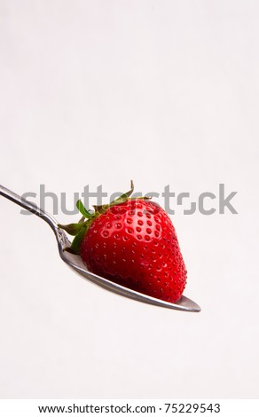 Spoonful of Strawberry Sitting in Spoon White Background Red Food Snack Fruit Silverware - stock photo