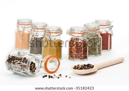 Spoonful of tropical peppercorns and filled spice jars - stock photo