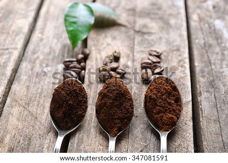 Spoons with coffee on wooden table, close up - stock photo