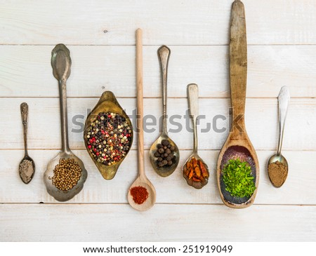 spoons with herbs and spices on white wooden background - stock photo