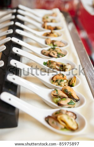 Spoons with mussels - a tasty banquet dish - stock photo